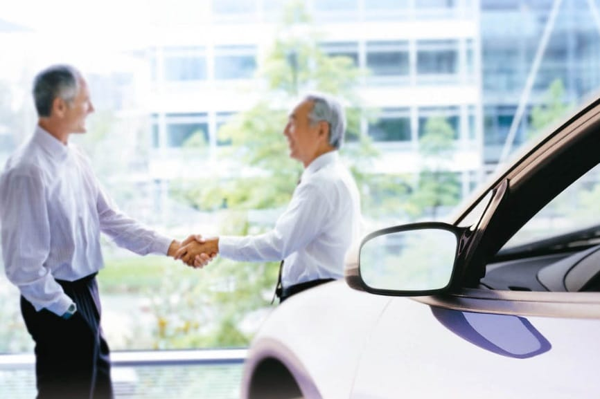 Hommes se serrant la main et une voiture