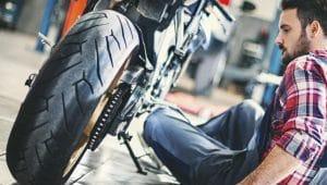 Homme assis à côté d'une moto