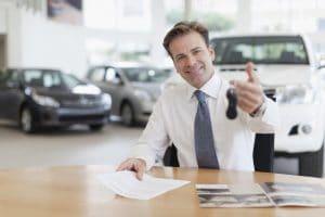 courtier automobile souriant tendant clefs de voiture